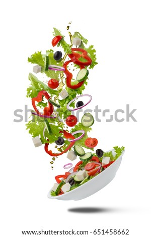 Flying Greek salad for on white . A white plate with falling out ingredients: olives, lettuce, onion, pepper, tomato, cucumber, cheese, and olive oil. Vegetarian menu