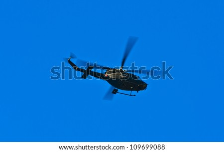 Flying helicopter on a blue sky