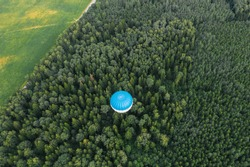 Flying hot air balloon over the green forest.