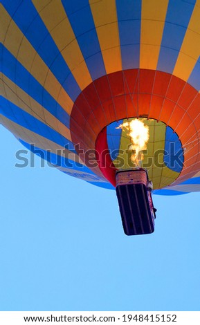 Flying in a hot air balloon, the flame of the burner fire heats the air, raising the balloon with a basket high into the sky, close-up, bottom view. Copy space, vertical image.