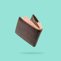 Flying in air Brown genuine leather wallet with banknotes and credit card inside isolated on turquoise background.