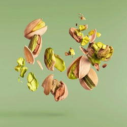 Flying in air fresh raw whole and cracked pistachios  isolated on green background. Concept of Pistachios is torn to pieces close-up. High resolution image