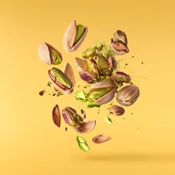 Flying in air fresh raw whole and cracked pistachios  isolated on yellow background. Concept of Pistachios is torn to pieces close-up. High resolution image
