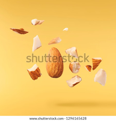 Flying in air fresh raw whole and cut almonds  isolated on yellow background. Concept of Almonds is torn to pieces close-up. High resolution image
