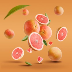Flying in air fresh ripe whole and cut grapefruit with seeds and leaves isolated on red background.