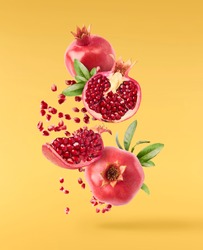 Flying in air fresh ripe whole and cut pomegranate with seeds and leaves isolated on yellow background. High resolution image