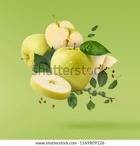 Flying in air Green fresh whole and cut apples and leaves over green background, food levitation concept, high quality