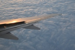 Flying in the sky, wing of the airplane in the sunset, flying in the clouds high in the sky, traveling and tourism, aviation industry and flights, spoilers, airborne, soaring high,