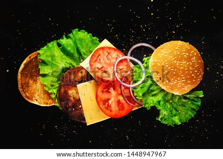Flying ingredients for a homemade burger on a black background. Not diet food, unhealthy food. #1448947967