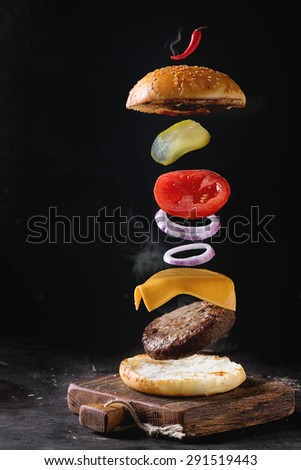 Flying ingredients for homemade burger on little wooden cutting board over dark background.