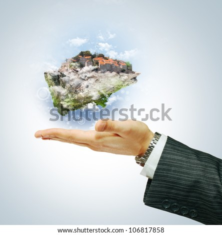 Flying island on businessman's hand