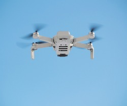 Flying multirotor with camera at clear blue sky background