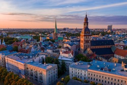 Flying over beautiful old town of Riga, Latvia at sunset with Domes cathedral and golden cock statue in the foreground.