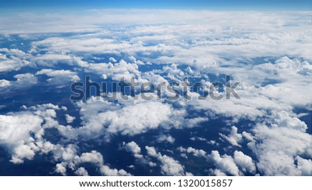 Flying over picturesque bright white and blue cloudscape. Beautiful moving clouds view from airplane window. Traveling through clear blue cloudscape. #1320015857