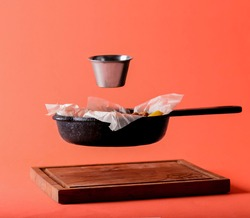 Flying pan with diner and a sauce pan over bright orange background. creative idea, concept. Wooden board, frying pan and a saucepan.