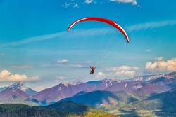 Flying paraglider from the Stranik hill over the mountainous landscape of the Zilina basin in the north of Slovakia. Mala Fatra National Park in the background, Slovakia, Europe.