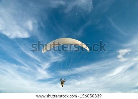 Flying paramotor under blue sky