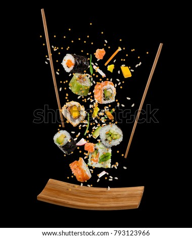 Flying pieces of sushi with wooden chopsticks and plate, isolated on black background. Flying food and motion concept. Very high resolution image