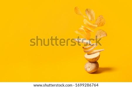 Flying potato slice into potato chips isolated on yellow background Foto stock ©