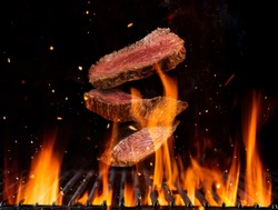 Flying raw beef steaks pieces above burning grill grid, isolated on black backround. Barbecue and grill concept