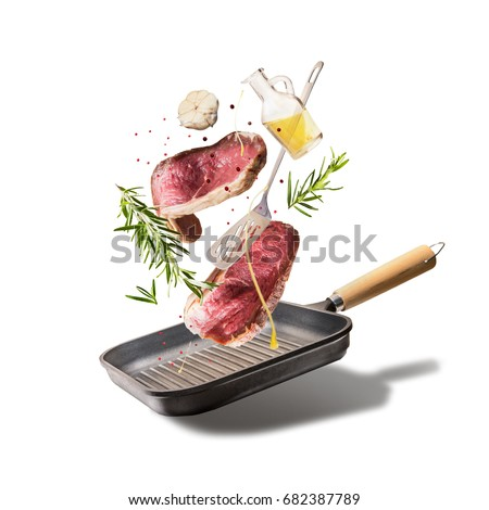 Flying raw beef steaks, with herbs, oil and spices with grill pan and kitchen utensils, isolated on white background, front view. Flying  food concept #682387789
