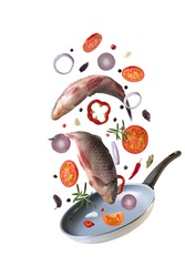 Flying raw whole  fishes  carp with vegetables and spices, ingredients above frying pan for tasty cooking on white background.