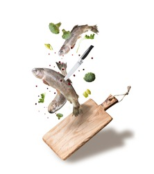 Flying raw whole trout fishes with vegetables, oil and spices ingredients above wooden cutting board for tasty cooking, isolated on white background. Healthy food or diet eating  concept.