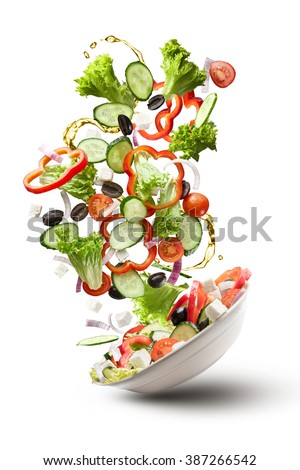 flying salad isolated on white background. Greek salad: red tomatoes, pepper, cheese, lettuce, cucumber, olives and olive oil #387266542