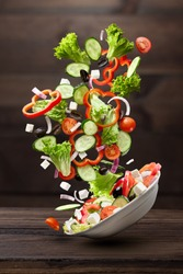 flying salad isolated on wooden background. Greek salad: red tomatoes, pepper, cheese, lettuce, cucumber and olives
