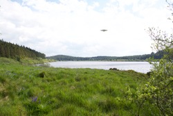Flying saucer UFO over lake in summer surrounded by green British landscape on a clear sunny day in the UK, CGI recreation