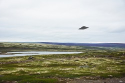 Flying saucer UFO over tundra in the Kola Peninsula in Russia. UFO floating above tundra landscape near Teriberka village