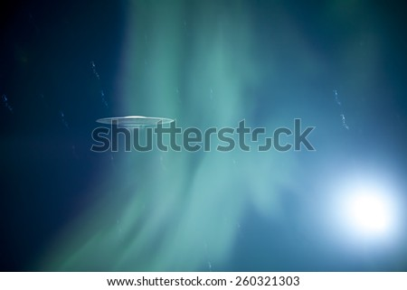 Flying Saucer with a glowing green aurora borealis and an odd glow.