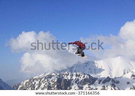Flying snowboarder on mountains. Extreme sport. #371166356