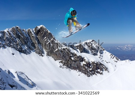 flying snowboarder on mountains. Extreme winter sport #341022569