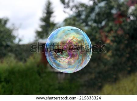 Flying soap bubble reflecting village house photo