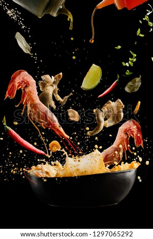 flying  soup tom yam with shrimp and spices. Concept of food preparation in low gravity mode, food levitation. Separated on black background. High resolution image