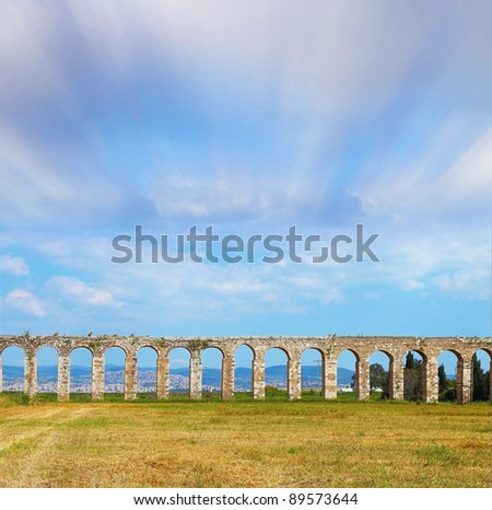 Flying spring clouds over the ruins of an ancient Roman aqueduct