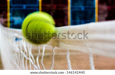 Flying tennis ball hits the white tennis net