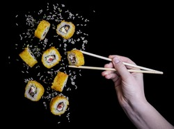 flying up yellow sushi tempura with rice on a black background their hand catches bamboo chopsticks