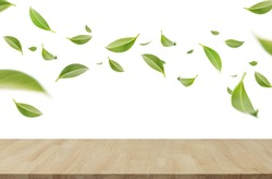 Flying whirl green leaves in the air with wooden table, Healthy products by organic natural ingredients concept, Empty space in studio shot isolated on white background long banner
