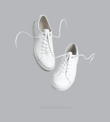 Flying white leather womens sneakers isolated on gray background. Fashionable stylish sports casual shoes. Creative minimalistic layout with footwear Mock up for your design Advertising for shoe store