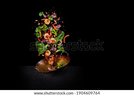 Flying wok ingredients - shrimp, vegetables, pak choi leaves, onions and peanuts. Asian food delivery. Chinese recipes. Wok preparation ingredients. Copy space