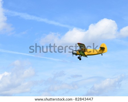 Flying yellow plane, biplane against blue sky