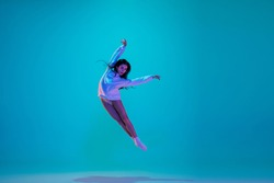 Flying. Young and graceful ballet dancer isolated on blue studio background in neon light. Art, motion, action, flexibility, inspiration concept. Flexible caucasian ballet dancer, moves in glow.