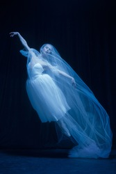 Flying. Young graceful beautiful woman, balerina in white wedding dress in art performance isolated on dark background in neon light. Concept of love, relationship, beauty, art and theater.