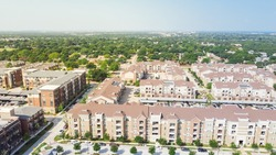 Flyover brand new multistory apartment complex with covered parking lots and suburban residential area in background. Master-planned community and census-designated sprawl in Flower Mound, TX