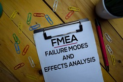 FMEA - Failure Modes and Effects Analysis write on a paperwork isolated on wooden background.