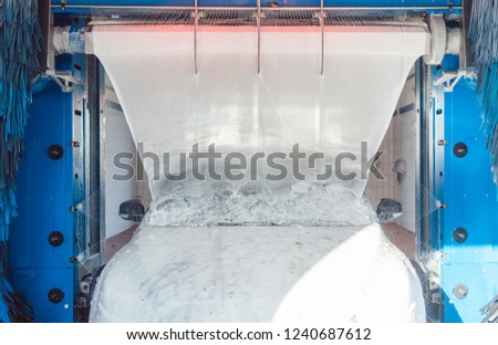 Foam being put on auto in car wash to clean it
