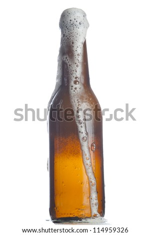 Foam coming out of beer bottle on white