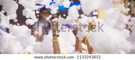 Foam party entertainment, people have fun raising hands catch soap bubbles, summer entertainment festival in aquapark, background or texture of white foam with copy space #1133243852